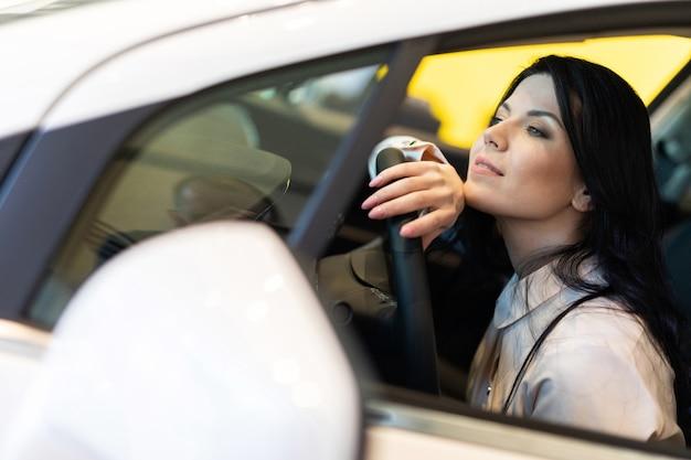 ディーラーセンターで新しい車を買う幸せな顧客女性 Premium写真