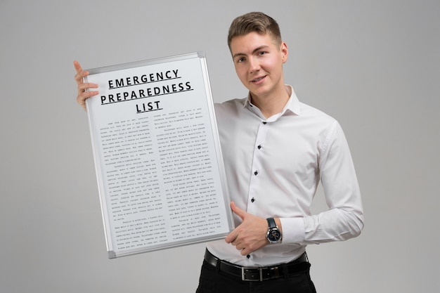 Молодой человек, держащий список аварийной готовности, изолированных на светлом фоне Premium Фотографии