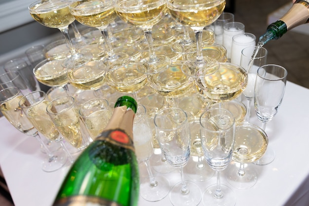 グラスにシャンパンを注ぐウェイターの手のクローズアップ Premium写真