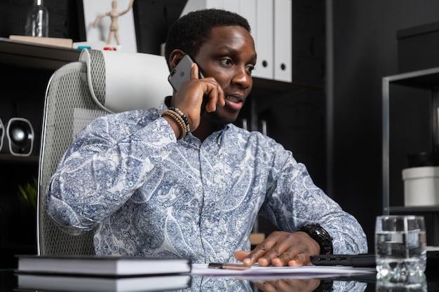 コンピューターに座って携帯電話を話している若い黒ビジネスマンオフィスの机 Premium写真