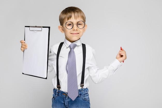 白いシャツ、サスペンダー、ネクタイ、軽いジーンズを着た魅力的な少年が灰色をしています。少年はペンとメモ用のシートを持っています Premium写真