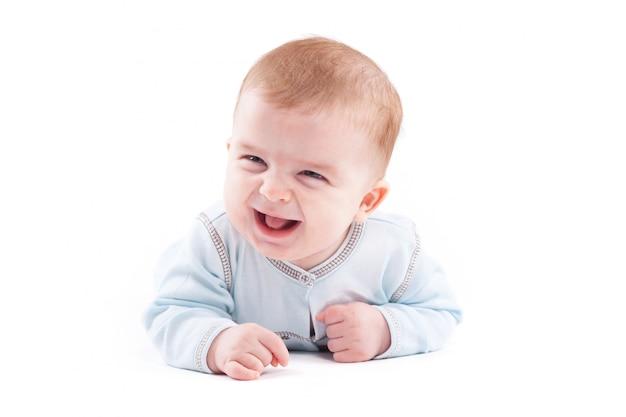 Милый симпатичный маленький мальчик в синей рубашке лежит на животе Premium Фотографии