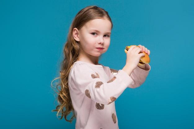 黒髪のセーターの可愛い、小さな女の子はハンバーガーを保持 Premium写真