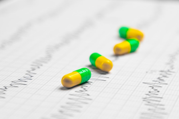 Разноцветные таблетки на листе экг Premium Фотографии