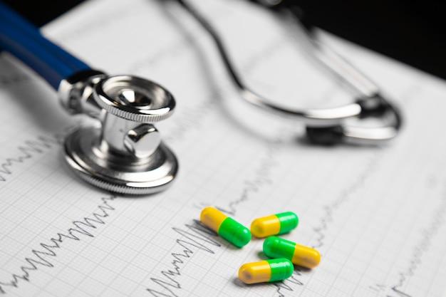 Стетоскоп и цветные таблетки, лежащие на листе с электрокардиограммой Premium Фотографии