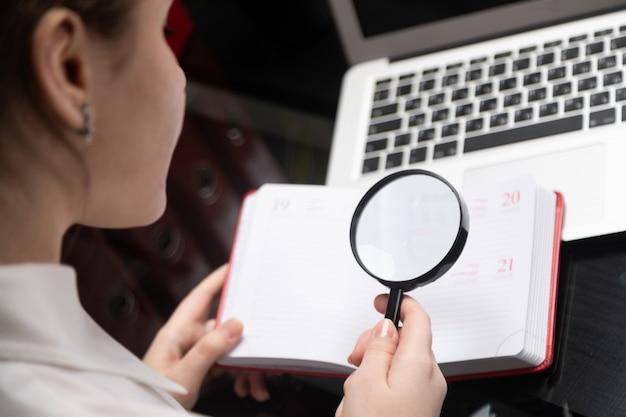 Молодая коммерсантка с лупой смотря дневник на предпосылке компьтер-книжки Premium Фотографии