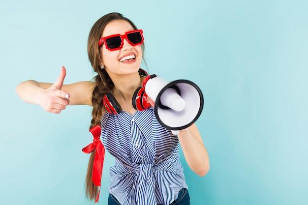 ヘッドフォンとスピーカーを持つ若い女性 Premium写真