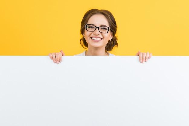 黄色の背景にブランクの看板を示す自信を持って美しい幸せな笑顔若いビジネス女性の肖像画 Premium写真