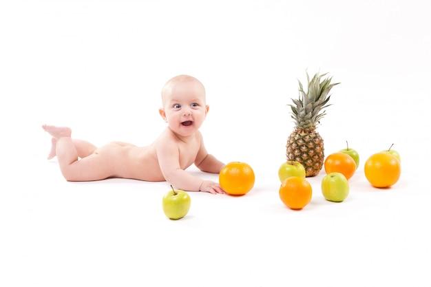 かわいい笑顔の健康な子供は、果物の中で白い背景にあります。 Premium写真