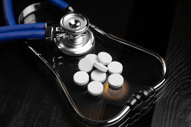 Стетоскоп и таблетки на черном столе Premium Фотографии