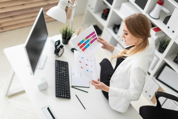 若い女性はテーブルの上の研究で身をかがめ、彼女の手で彫刻と図表でドキュメントを保持します。 Premium写真
