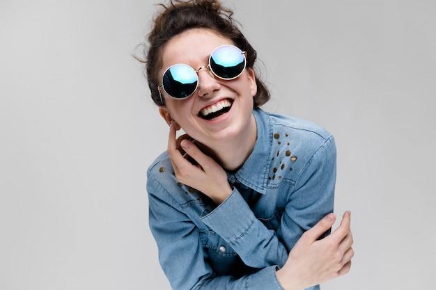 Молодая брюнетка девушка в круглых очках. волосы собраны в булочку. девушка приложила руку к голове. Premium Фотографии