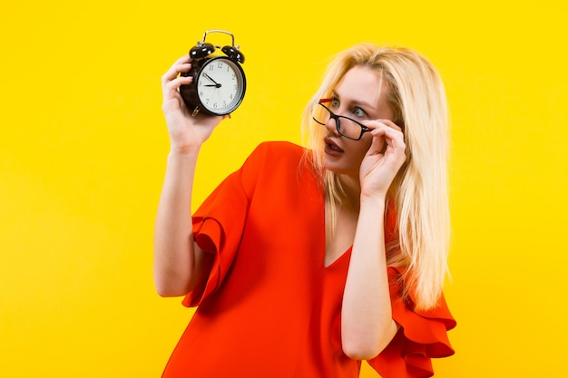 目覚まし時計を保持している金髪の女性 Premium写真