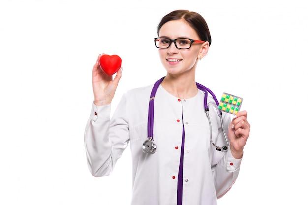 白い背景の上の彼女の手で心と薬を保持している若い美しい女性医師 Premium写真