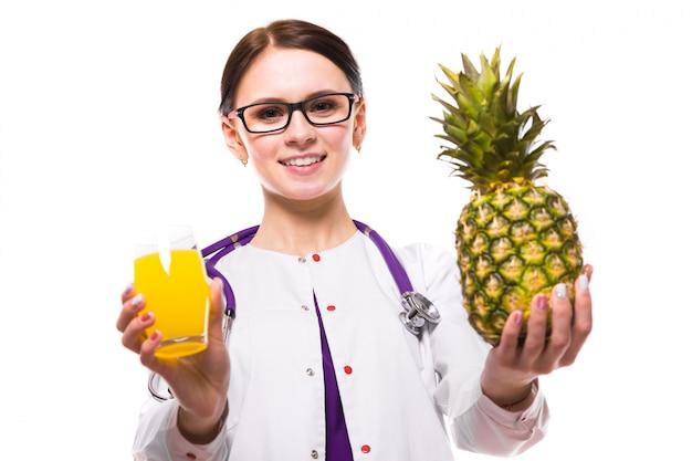 女性栄養士は、白い背景の上の彼女の手でパイナップルとフレッシュジュースのガラスを保持します。 Premium写真