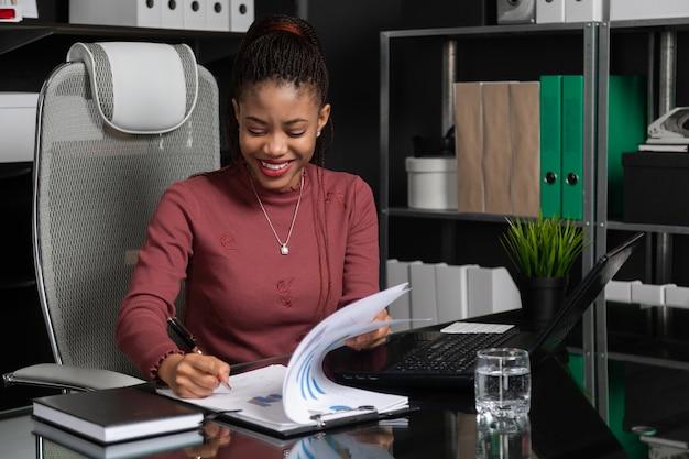 壮大な若い黒の実業家がオフィスのテーブルでドキュメントに署名します Premium写真
