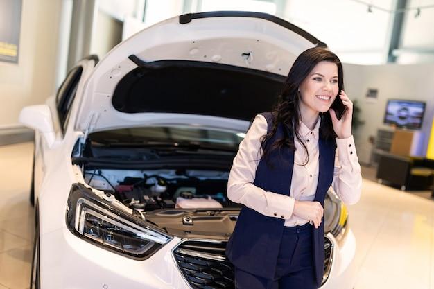 Красивая распродажа осматривает новую машину и разговаривает по телефону в автосалоне автосалона Premium Фотографии