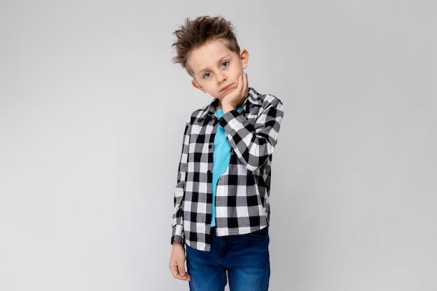 格子縞のシャツ、青いシャツとジーンズでハンサムな男の子 Premium写真