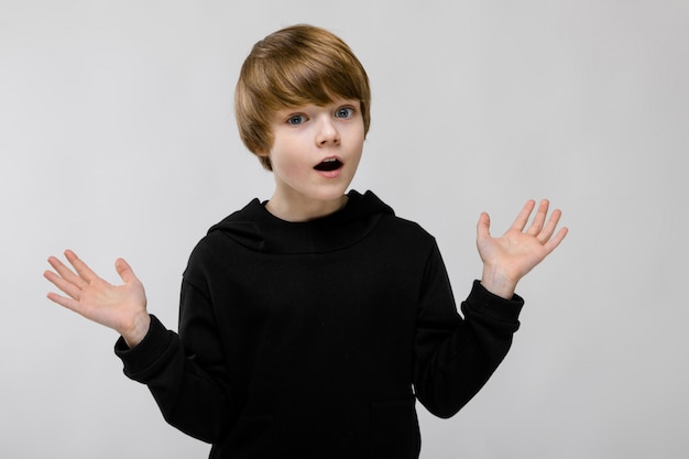 口を開けて、両手を広げて愛らしい驚いた少年の肖像画 Premium写真