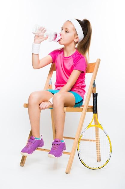 白のテニスラケットでかわいい女の子 Premium写真