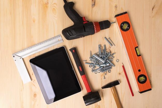 軽い木製のテーブルに横たわる構築ツールとデジタルタブレット Premium写真