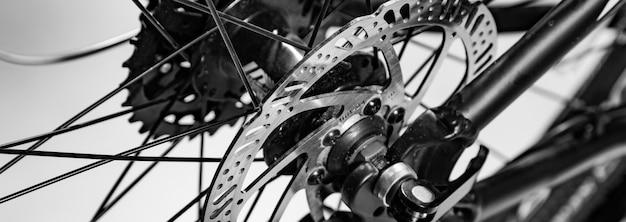 白と黒の自転車で名前付きのメカニックブレーキディスクのクローズアップショット Premium写真