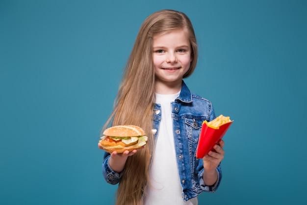 長い茶色の髪とジャンジャケットのかわいい女の子は、ハンバーガーとフライドポテトを保持します。 Premium写真