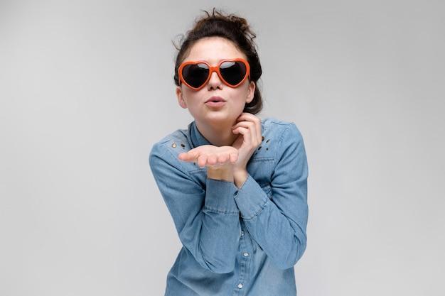 ハートの形の眼鏡の若いブルネットの少女。毛はパンに集められます。女の子は空中キスを送ります。 Premium写真