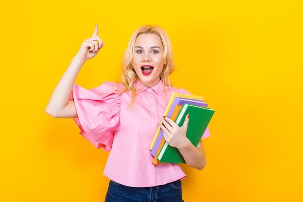 Блондинка в розовой блузке с кучей книг Premium Фотографии