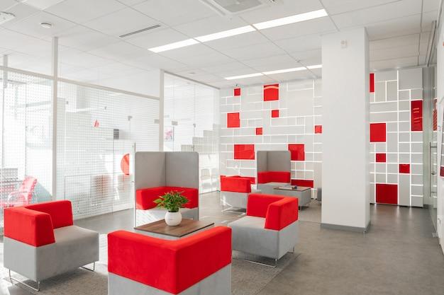 白い壁、灰色の床、赤と白の肘掛け椅子付きのオープンスペース、ガラスの壁の向こうの部屋を備えたモダンなオフィスのコーナー Premium写真