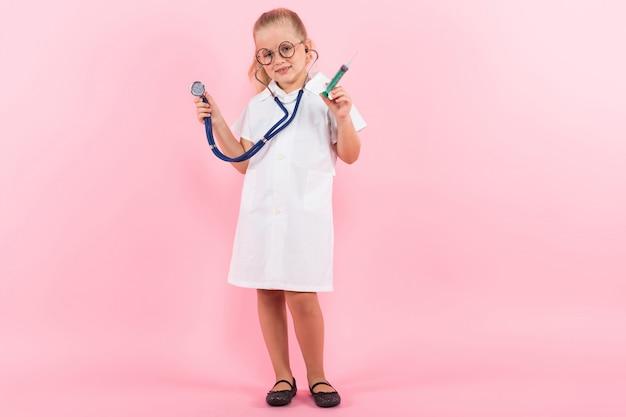 Маленькая девочка в костюме доктора с инъекцией Premium Фотографии