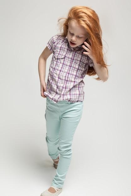 格子縞のシャツ、明るい青いズボン、白いブーツの愛らしいかわいい赤毛の女の子 Premium写真