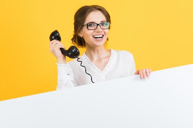 Портрет уверенно красивые возбужденные улыбающиеся счастливые молодые деловая женщина с телефоном, показывая пустой рекламный щит на желтом фоне Premium Фотографии