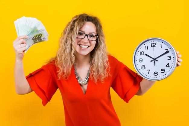 時計と紙幣のファンのドレスを着た女性 Premium写真