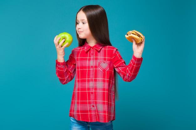 黒髪の市松模様のシャツを着たかわいい女の子がハンバーガーを保持 Premium写真