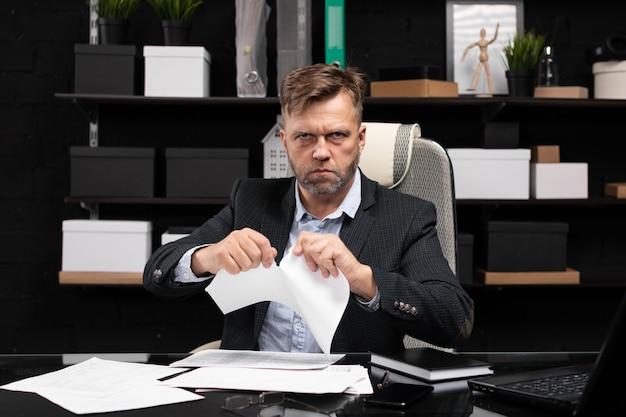 コンピューターのテーブルと涙のドキュメントに座っているビジネスマン Premium写真
