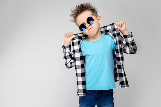 格子縞のシャツ、青いシャツ、ジーンズでハンサムな男の子は灰色の背景に立っています。少年は丸眼鏡をかけています。彼の指の襟のシャツを保持している赤毛の少年 Premium写真