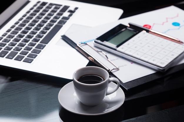 モダンな電卓はノートとシートにあり、コーヒーカップの横にスケジュールがあります Premium写真