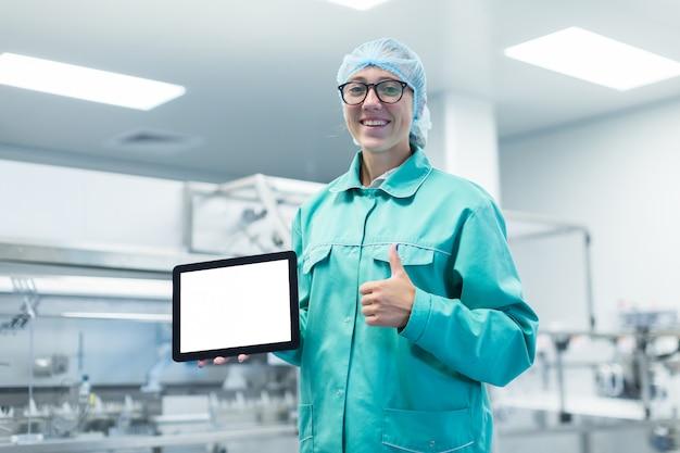 彼の手にタブレットを持つ製薬工場労働者は機器を示しています Premium写真