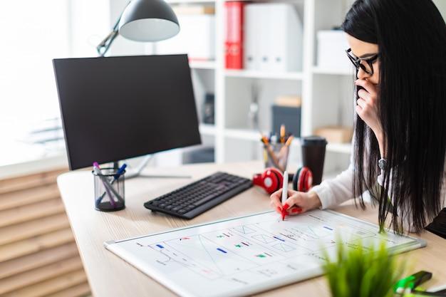 メガネをかけた若い女の子がテーブルのそばに立ち、マーカーを手に持って、磁気ボードに描きます。 Premium写真