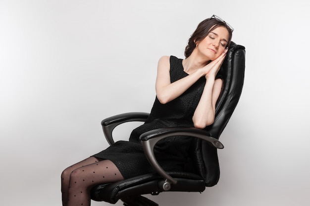 Картина красивая женщина в черном платье, сидя в кресле Premium Фотографии