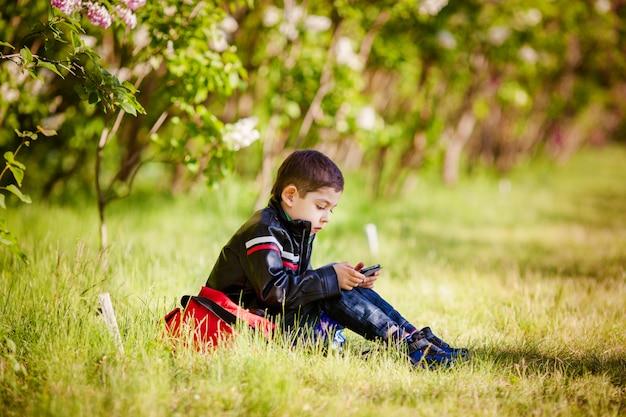 春の公園の芝生の上に座っている小さな男の子 Premium写真