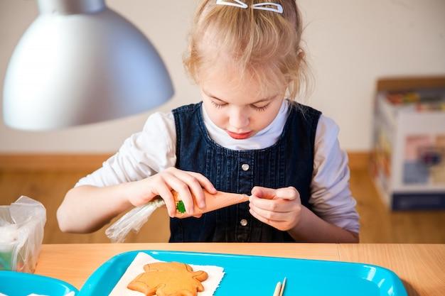 ジンジャーブレッドの装飾に関するワークショップで小さな女の子 Premium写真