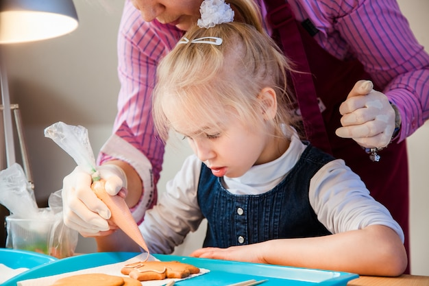 娘と彼女の母親が砂糖のアイシングでジンジャーブレッドを飾る Premium写真