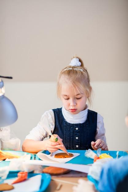 女の子は砂糖のアイシングでジンジャーブレッドを飾ることを学びます Premium写真