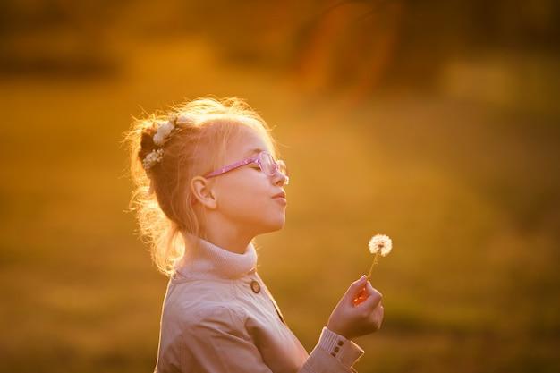 メガネと日没の秋の公園でタンポポで遊ぶ薄手のコートで巻き毛の女子高生 Premium写真