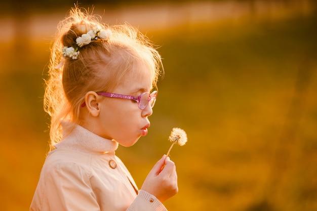 日没の秋の公園でタンポポで吹くメガネと光のコートで巻き毛の女子高生 Premium写真