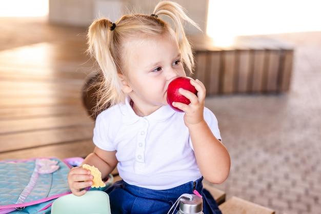 座っていると食べるかわいいかわいい白人幼児の赤ちゃん女の子 Premium写真