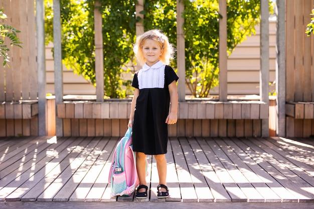 Счастливая маленькая школьница с обедом, книгой и карандашами. снова в школу на открытом воздухе Premium Фотографии