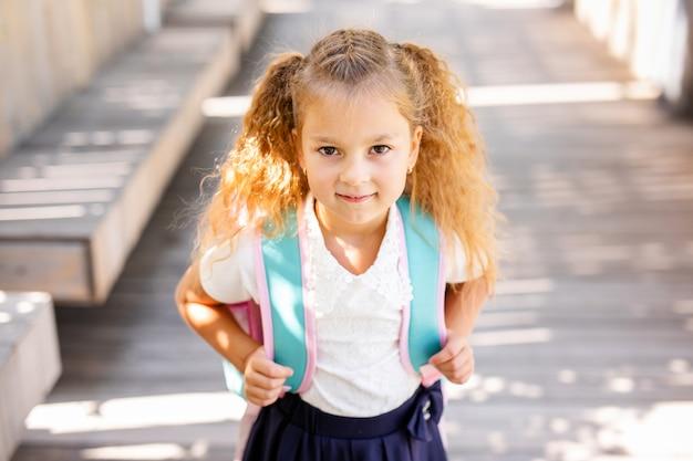 Счастливый маленькая школьница с яблоком. снова в школу на улице Premium Фотографии